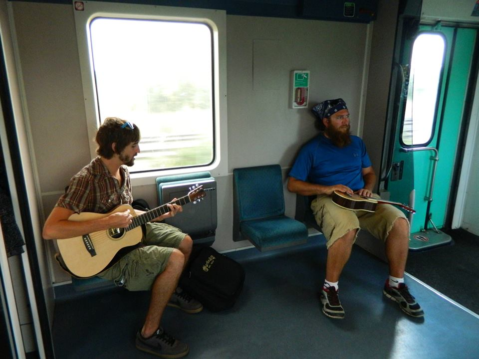 Tom from Tune Up and Travel, playing music on a train in France with his travel buddy Corey  (Image Credit: Tom Edwards)