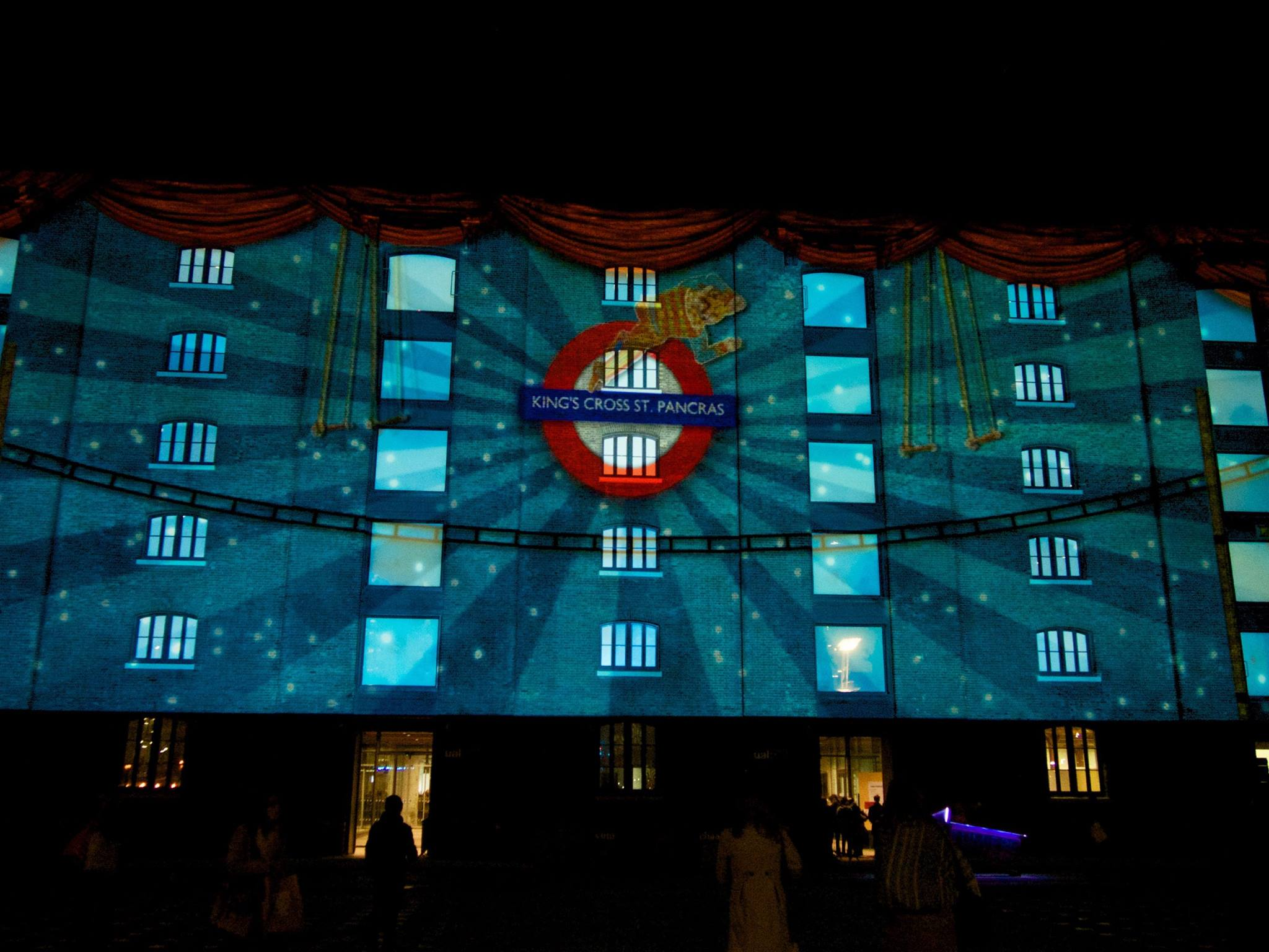 Playing on the wall of a building at Kings Cross station was the circus of light. An interactive circus show