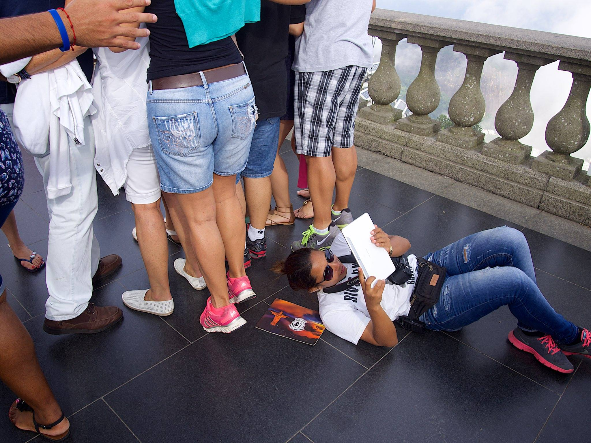 A tourist attempting to get a good shot of Christ the Redeemer